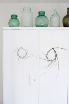 white bedroom and green vintage vases and green wreath