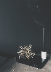 moody still with black wall, dried flowers and black candle