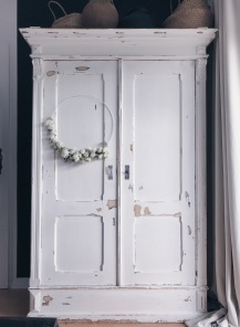 white shabby chic cupboard with a white wreath