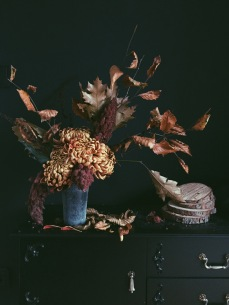 moody autumnal flower arrangement with chrysanthemums and dried leaves