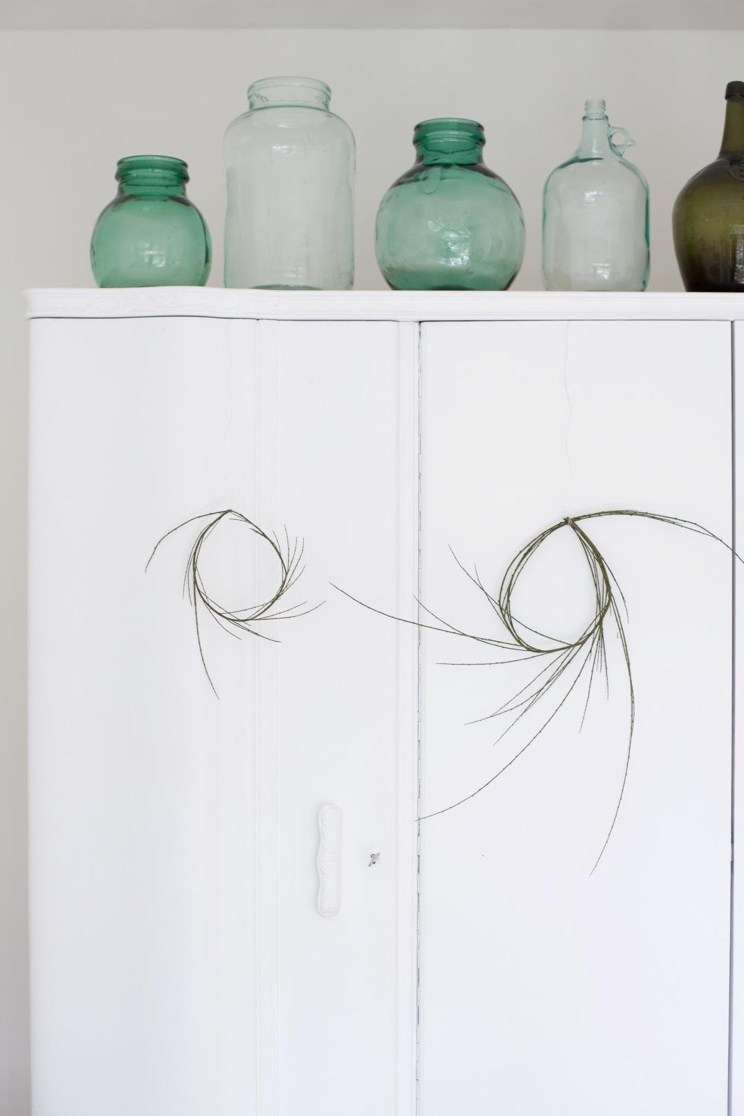 White bedroom, green vintage bottles & wreaths