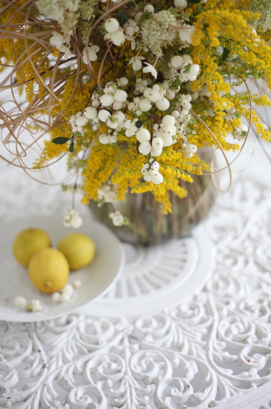 late summer flower arrangement with wild yellow flowers and snowberries
